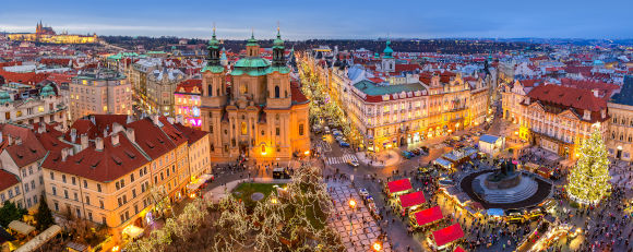 Panoramic view from above of city skyline, illuminated buildings and traditional Christmas market on Old Town Square